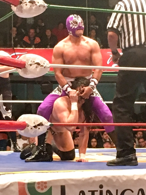 Mexican wrestler pulling another guy by the nostrils
